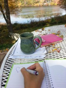 writing in notebook with mug and view