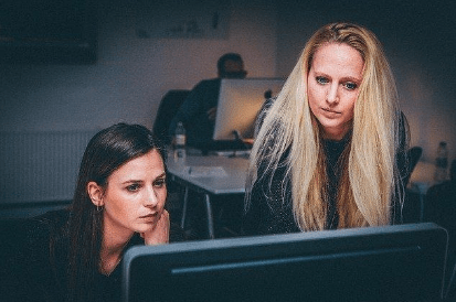 Two women looking at computer to research ghostwriter